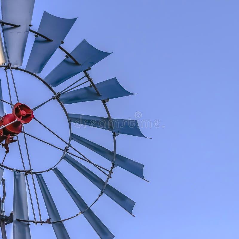 Fyrkantigt slut för ram upp av de åtskilliga bladen av en windpump med klar bakgrund för blå himmel arkivfoto