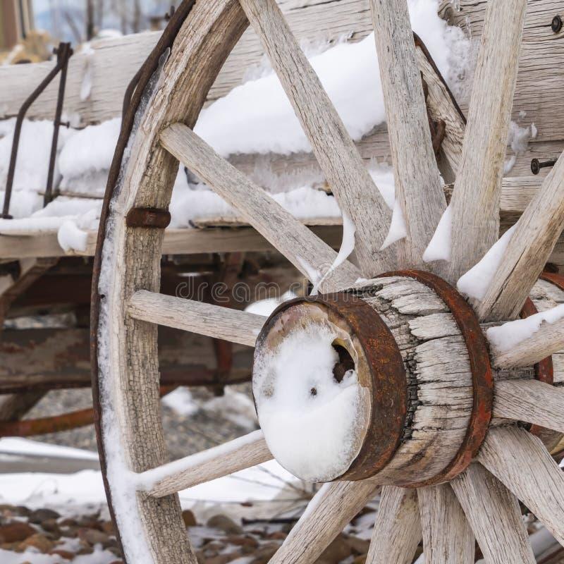 Fyrkantigt slut upp av de rostiga hjulen av en riden ut trävagn som beskådas i vinter arkivfoton