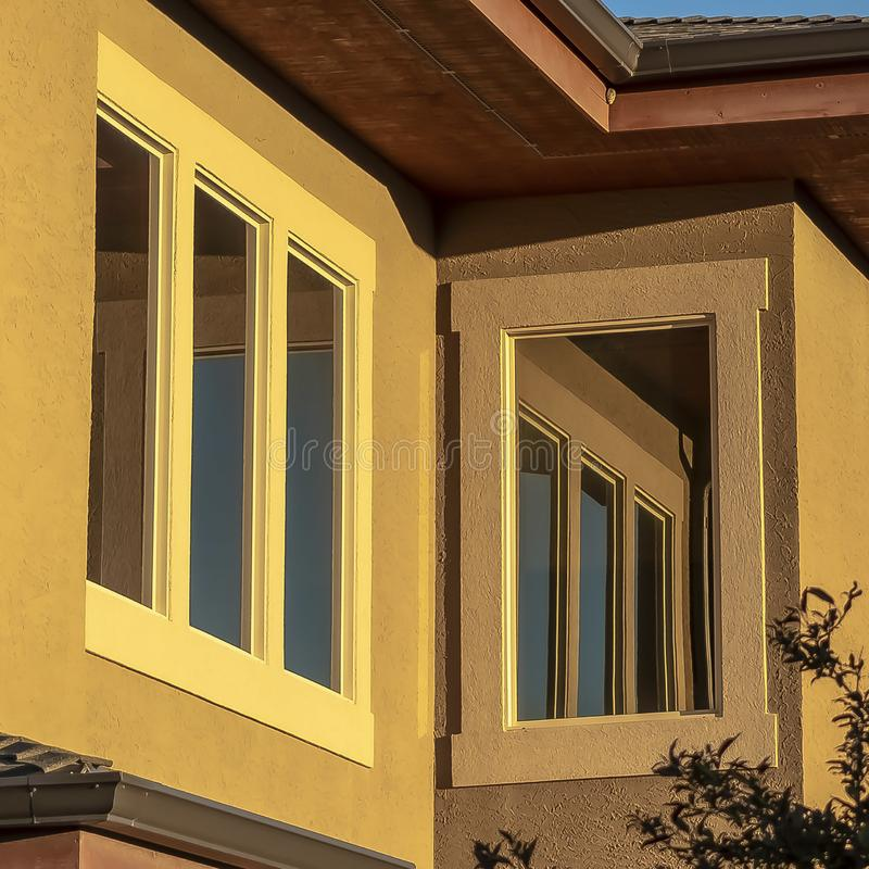 Fyrkantigt slut upp av en hem- övrevåningsyttersida med träd och blå himmel på en solig dag royaltyfria bilder