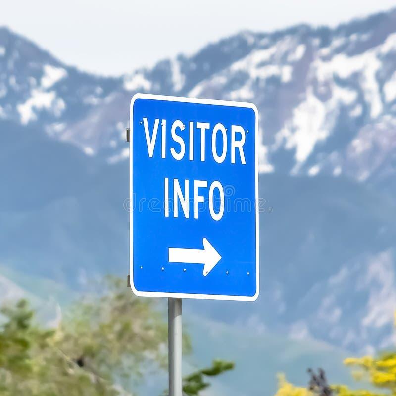 Fyrkantigt slut upp av ett informationstecken om besökare med träd snöig berg- och himmelbakgrund arkivbilder