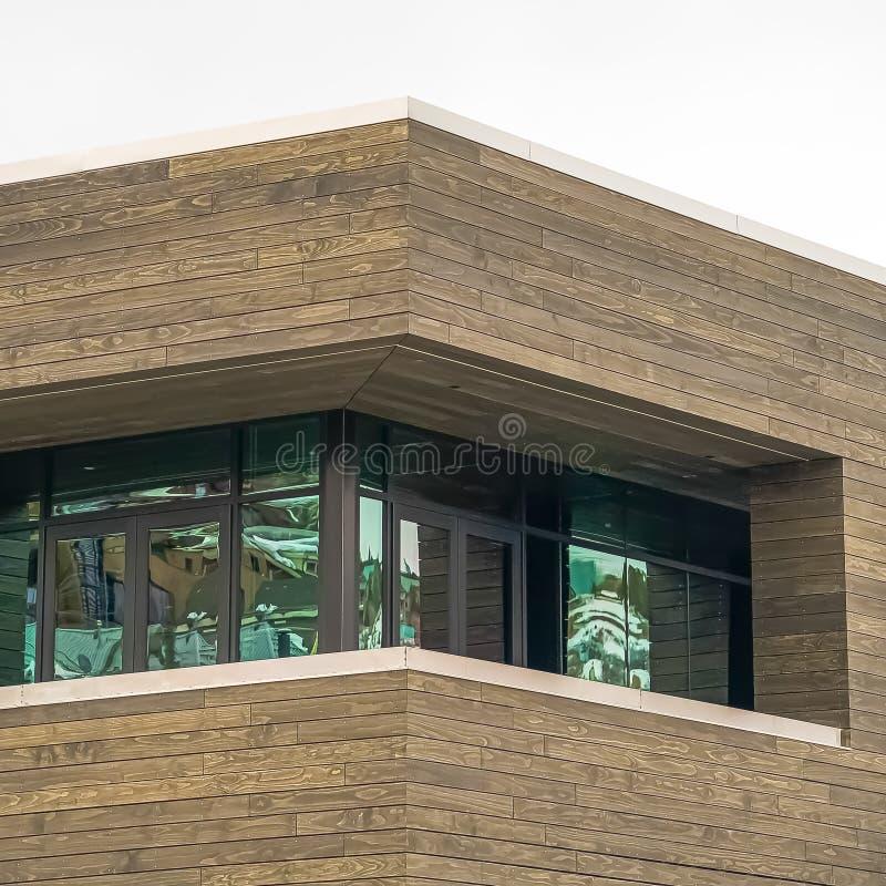 Fyrkantigt slut upp sikt av en byggnad med den bruna träväggen mot ljus vit himmel arkivfoto