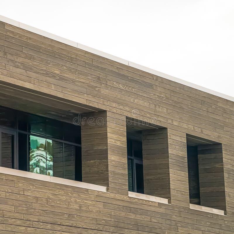 Fyrkantigt slut upp sikt av en byggnad med den bruna träväggen mot ljus vit himmel royaltyfria bilder