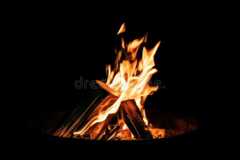 Fyrpanna- eller brandbunken med brinnande trä loggar in framdelen av svarta lodisar arkivfoto