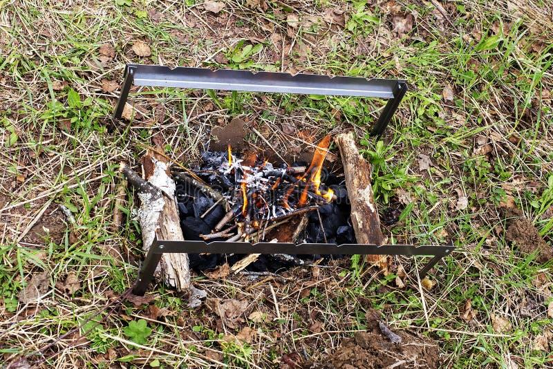Fyrpannan med bränningbrandträ står på gräset royaltyfri foto