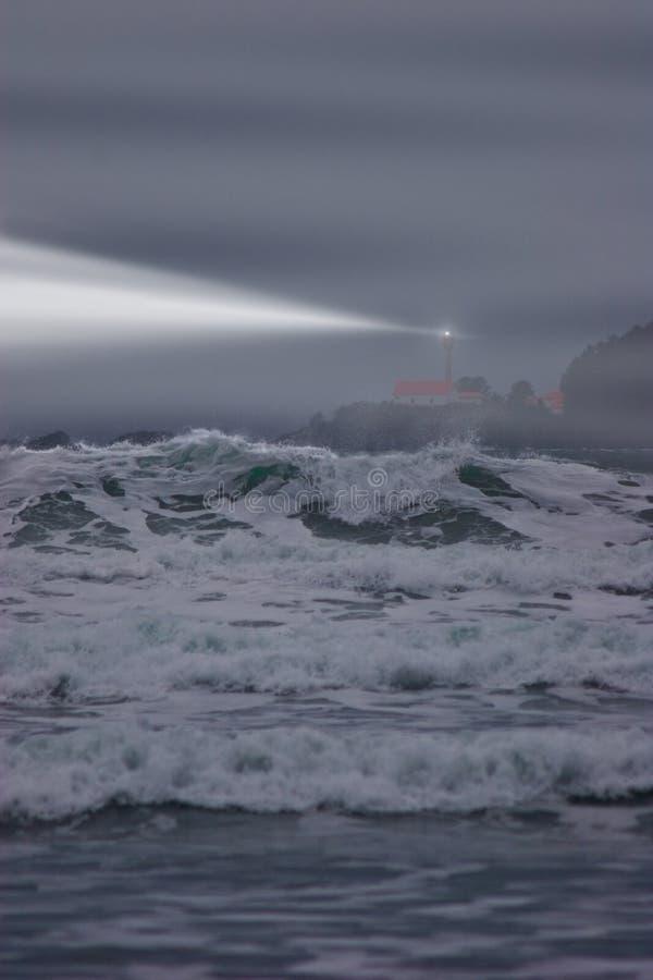 Fyrstrålen klipper igenom dimman på en stormig afton arkivfoton