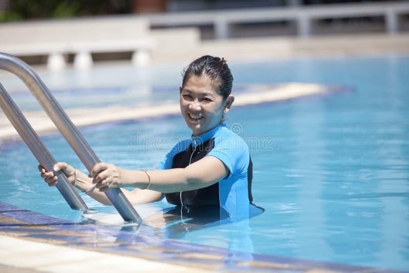 Fyrtio år gammal kvinna i simbassäng arkivfoton