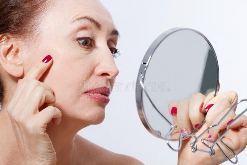 Fyrtio år gammal kvinna som ser skrynklor i spegel Plastikkirurgi- och collageninjektioner makeup Makroframsida Selektiv framsida royaltyfri fotografi
