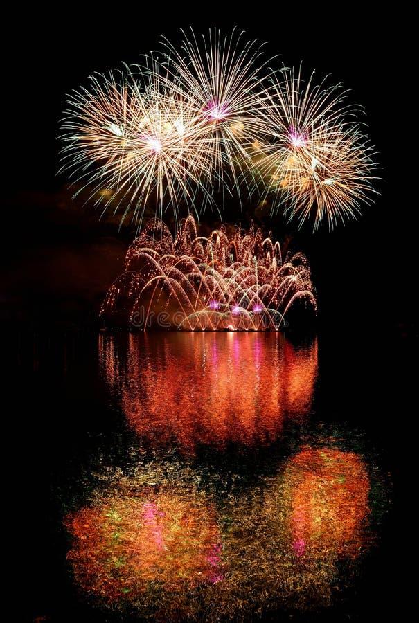 fyrverkeri Härliga färgrika fyrverkerier på vattenyttersidan med en rengöring svärtar bakgrund Rolig festival och strid av brandm arkivbilder