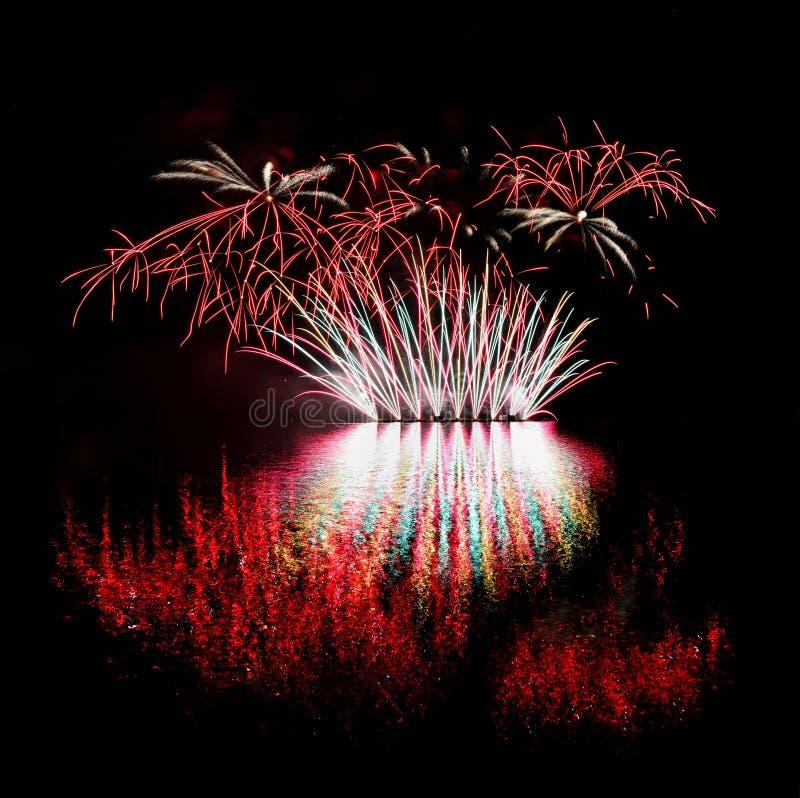 fyrverkeri Härliga färgrika fyrverkerier på vattenyttersidan med en rengöring svärtar bakgrund Rolig festival och strid av brandm royaltyfria foton