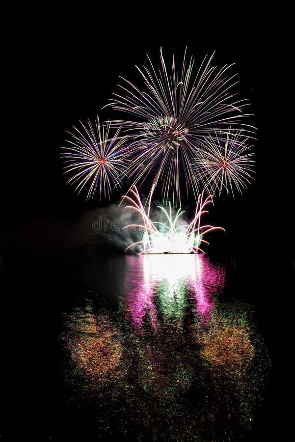 fyrverkeri Härliga färgrika fyrverkerier på vattenyttersidan med en rengöring svärtar bakgrund Rolig festival och strid av brandm royaltyfri bild