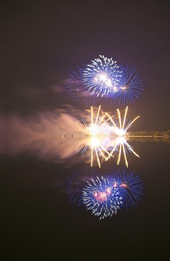 Fyrverkeri med reflexion i ett vatten fotografering för bildbyråer