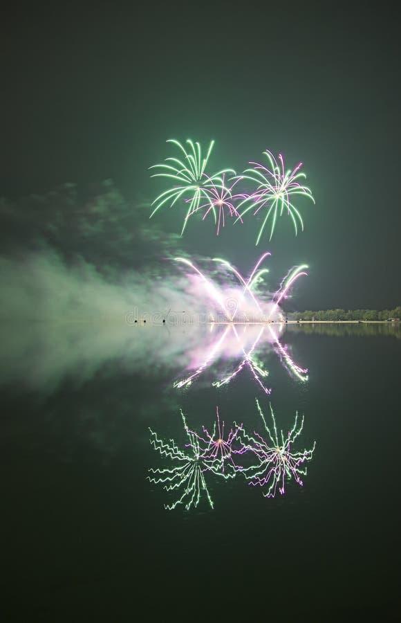 Fyrverkeri med reflexion i ett vatten royaltyfri fotografi