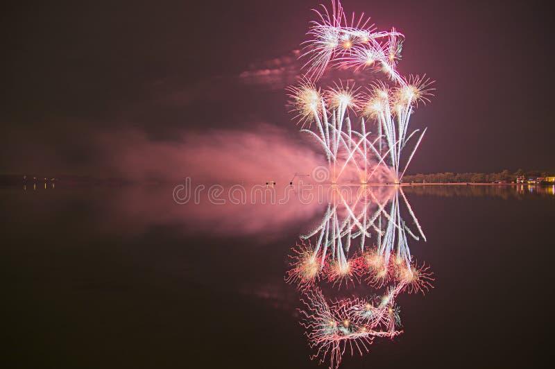 Fyrverkeri med reflexion i ett vatten royaltyfri foto