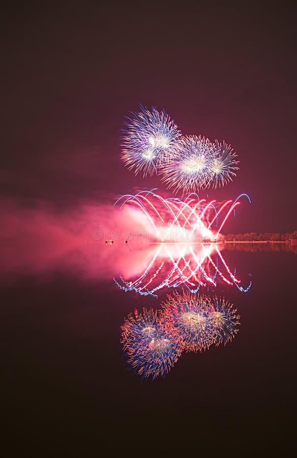 Fyrverkeri med reflexion i ett vatten arkivfoton