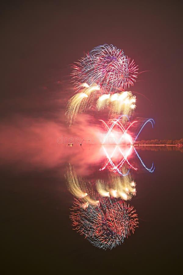 Fyrverkeri med reflexion i ett vatten royaltyfri bild