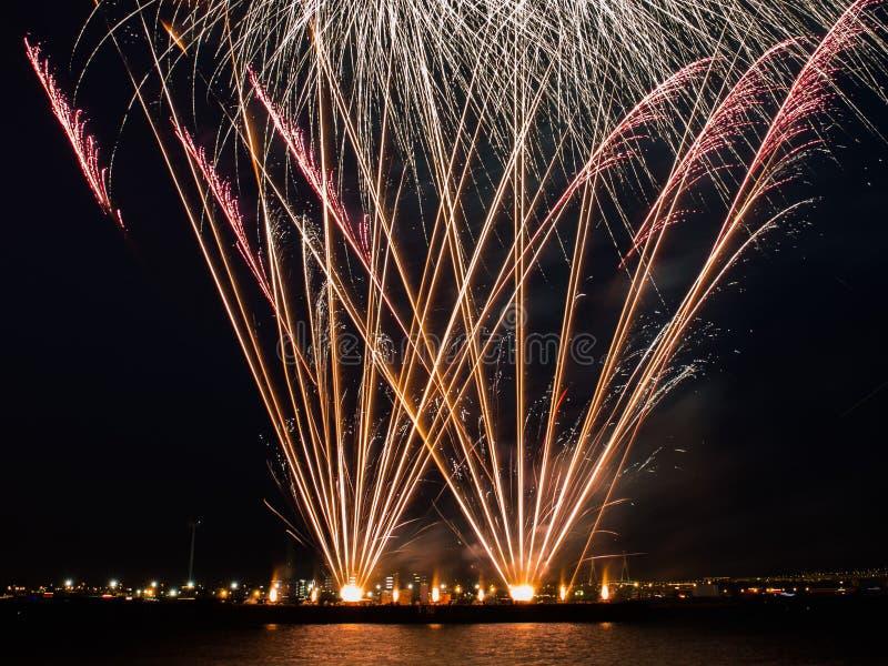 Fyrverkeribristning i natthimlen med ljusslingor och frikändgrunden av fyrverkerier över havet arkivbild