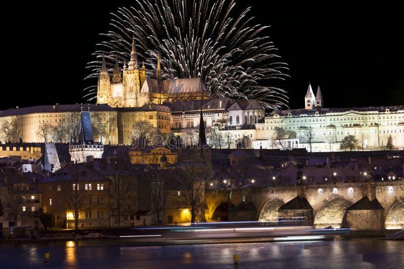 Fyrverkerier ovanför den färgrika snöig Prague för natt gotiska slotten med Charles Bridge, Tjeckien royaltyfria bilder