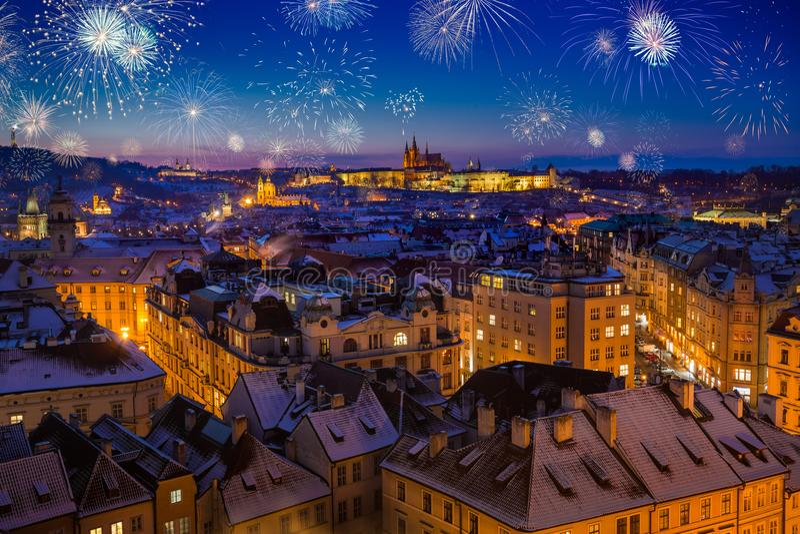 Fyrverkerier ovanför den Prague slotten med snöig tak under sen julsolnedgång arkivbild