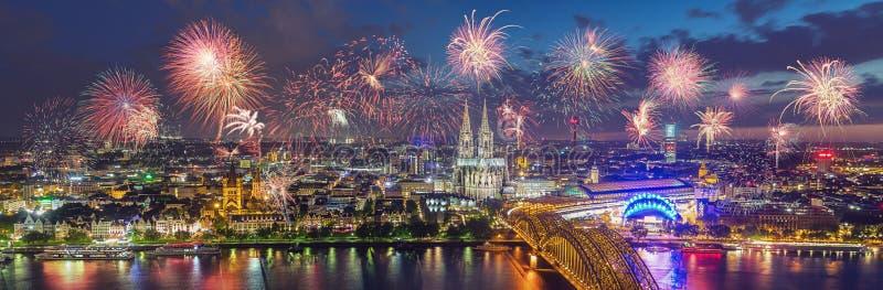 Fyrverkerier på Cologne horisont med domkyrkan och Hohenzollern Bri royaltyfri fotografi