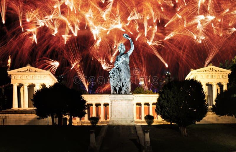 Fyrverkerier på den upplysta Bayern skulpturen i Munich arkivfoton