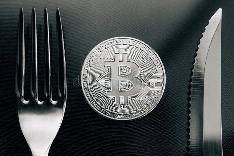 Fysiek zilveren Crytocurrency-Muntstuk tussen vork en knive stock foto's