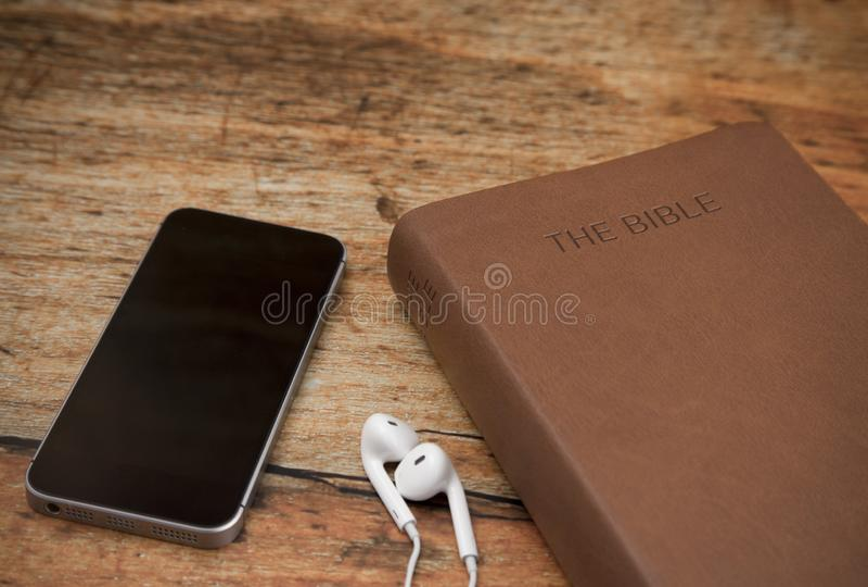 Fysieke Bijbel en een Slimme Telefoon met Oortelefoons royalty-vrije stock afbeelding