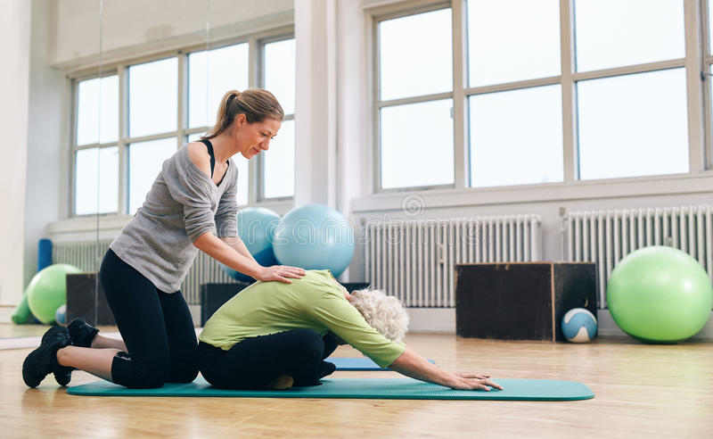 Fysieke trainer die oudere vrouw helpen die yoga doen royalty-vrije stock foto's