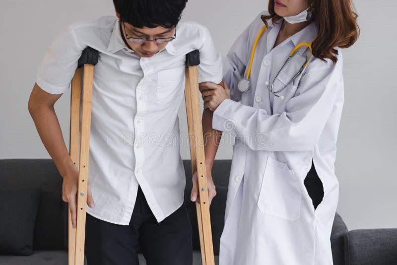 Fysieke vrouwelijke arts die patiënt met steunpilaren in het ziekenhuisbureau helpen royalty-vrije stock afbeelding