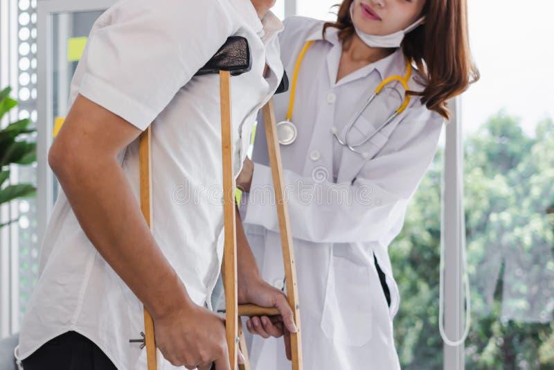 Fysieke vrouwelijke arts die patiënt met steunpilaren in het ziekenhuisbureau helpen stock fotografie