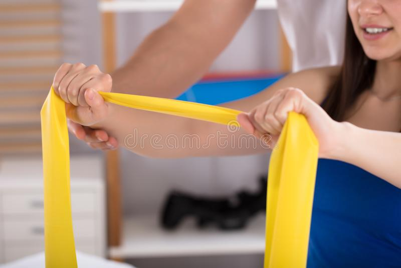 Fysioterapeut Assisting Woman While som gör övning arkivbild