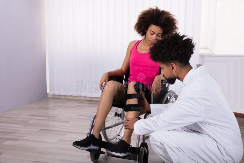 Fysioterapeut Fixing Knee Braces på benet för kvinna` s arkivbild