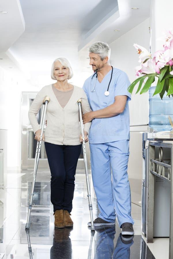 Fysioterapeut Helping Senior Woman med kryckor arkivbild