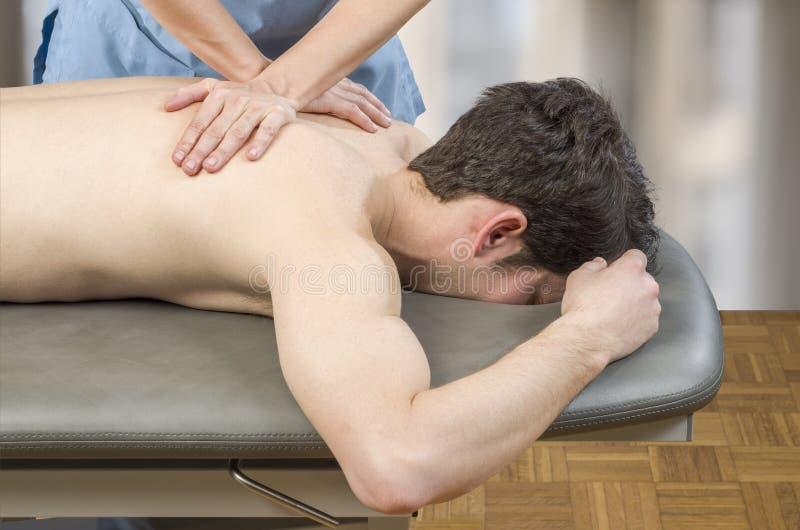 Fysioterapeut kiropraktor som ger en tillbaka massage till manpatienten osteopathy royaltyfri bild