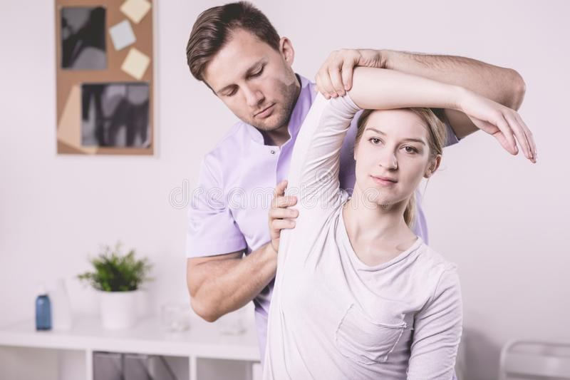 Fysioterapeut och patient som övar med armen under sjukgymnastik royaltyfria bilder