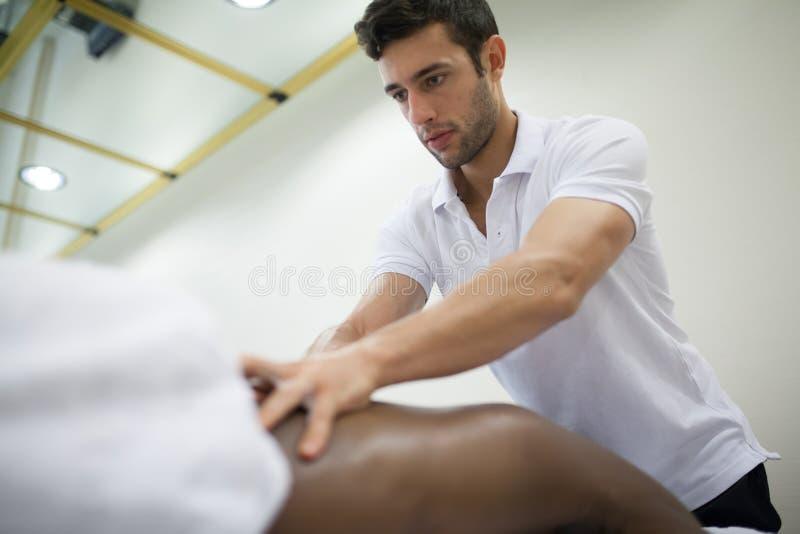 Fysioterapeut som applicerar massage fotografering för bildbyråer