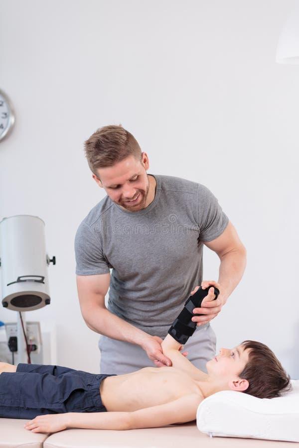Fysioterapeut som arbetar med den lilla patienten arkivfoto