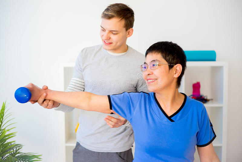 Fysioterapeut som arbetar med patienten royaltyfri fotografi