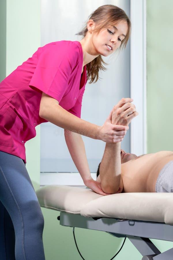 Fysioterapeut som behandlar tennisarmbågen royaltyfri fotografi