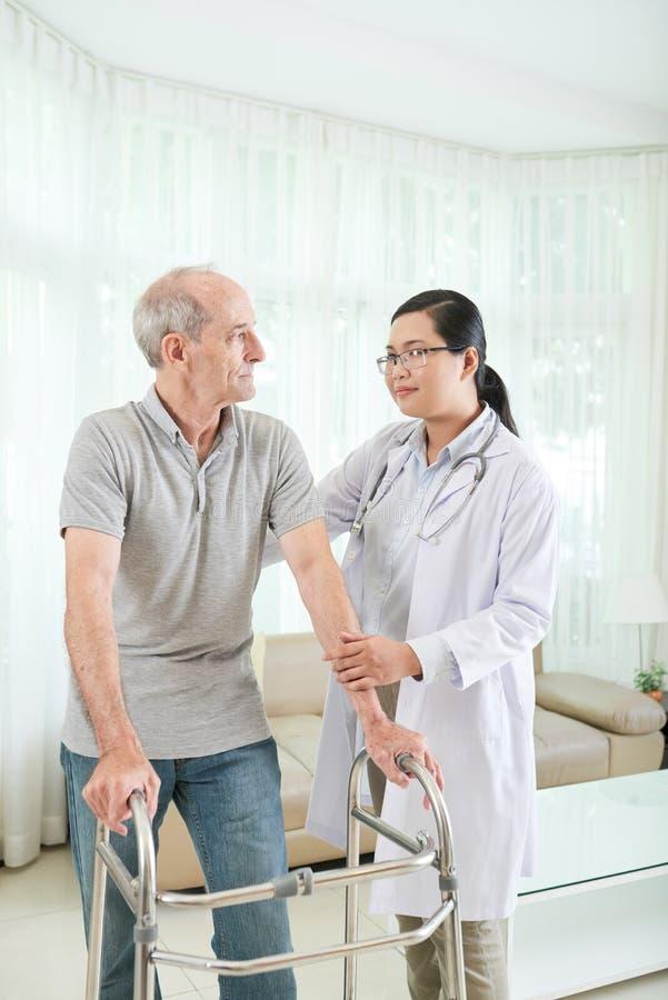 Fysioterapeut som besöker patienten royaltyfri bild