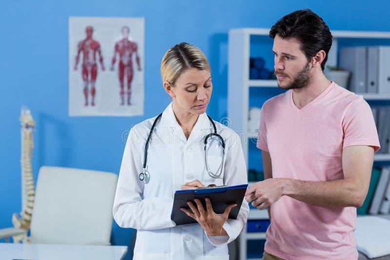 Fysioterapeut som förklarar diagnos till den manliga patienten arkivfoto