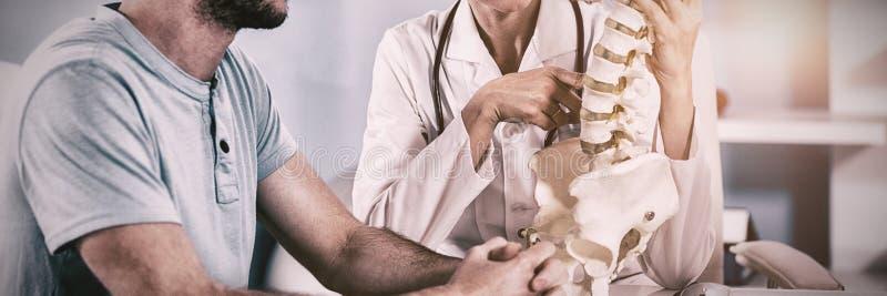 Fysioterapeut som förklarar inbindningsmodellen till patienten arkivfoton
