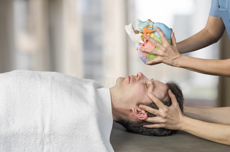 Fysioterapeut som gör en kranie- sacral terapi till en manpatient fotografering för bildbyråer