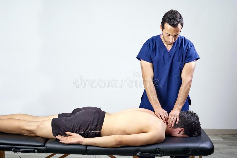 Fysioterapeut som gör en mobiliseringhals av den kvinnliga patienten Manuell terapi Neurological fysisk undersökning Osteopathy royaltyfria bilder