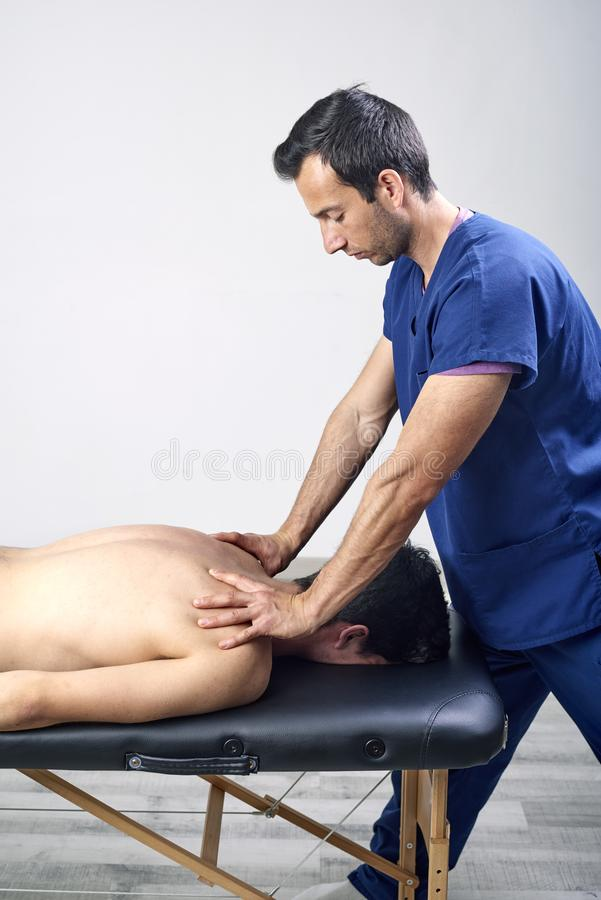 Fysioterapeut som gör en mobiliseringhals av den kvinnliga patienten Manuell terapi Neurological fysisk undersökning Osteopathy arkivbilder