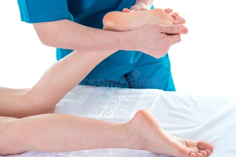Fysioterapeut som gör fotmassage på kliniken, closeup arkivfoto