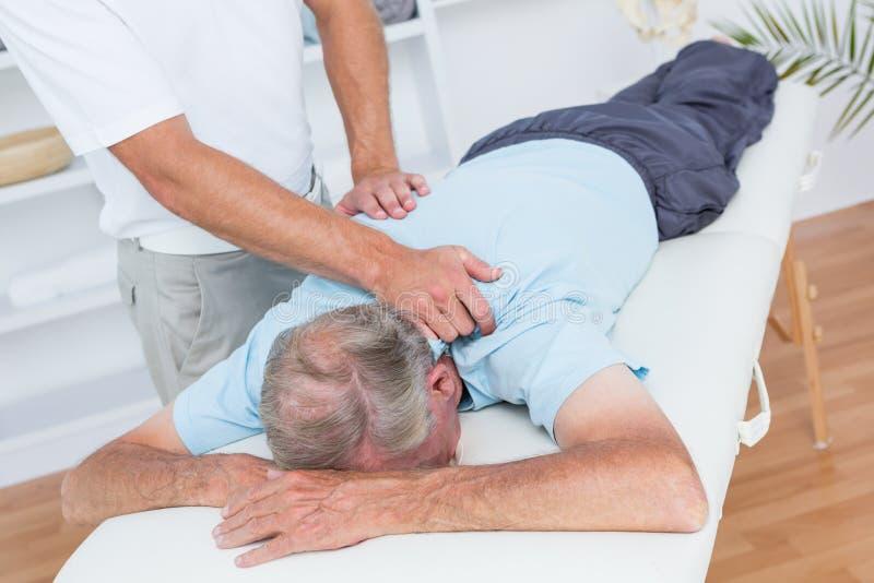 Fysioterapeut som gör halsmassage till hans patient arkivfoton