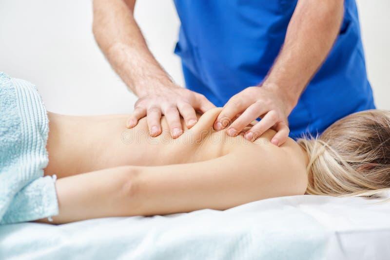 Fysioterapeut som gör läka behandling på mans baksida Terapeut som bär den blåa likformign osteopathy chiropractic arkivbilder