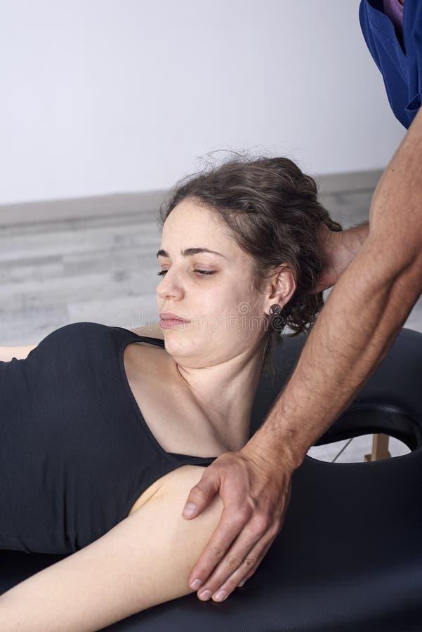 Fysioterapeut som g?r en mobiliseringhals av den kvinnliga patienten Manuell terapi Neurological fysisk unders?kning Osteopathy arkivfoto