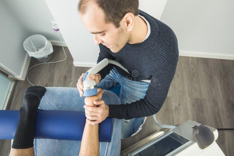 Fysioterapeut som ger fotterapi till en patient i kliniken Avancerat sjukgymnastikbegrepp arkivbilder