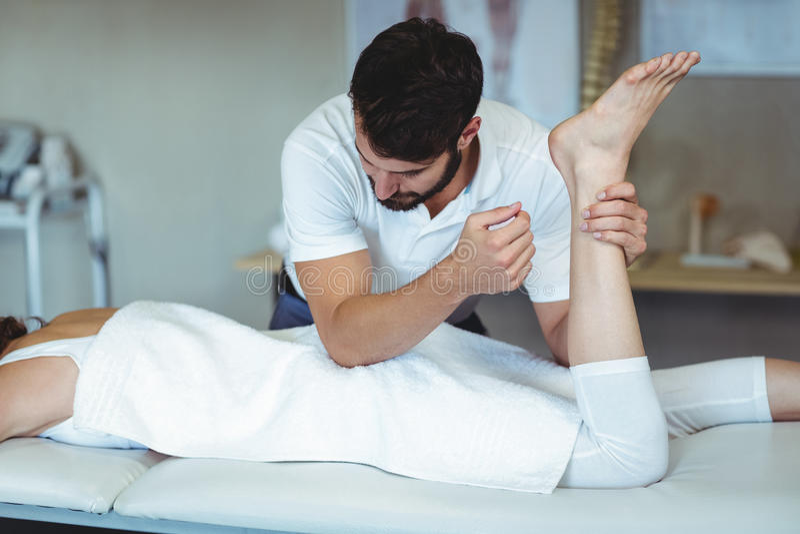 Fysioterapeut som ger höftmassage till en kvinna royaltyfria foton